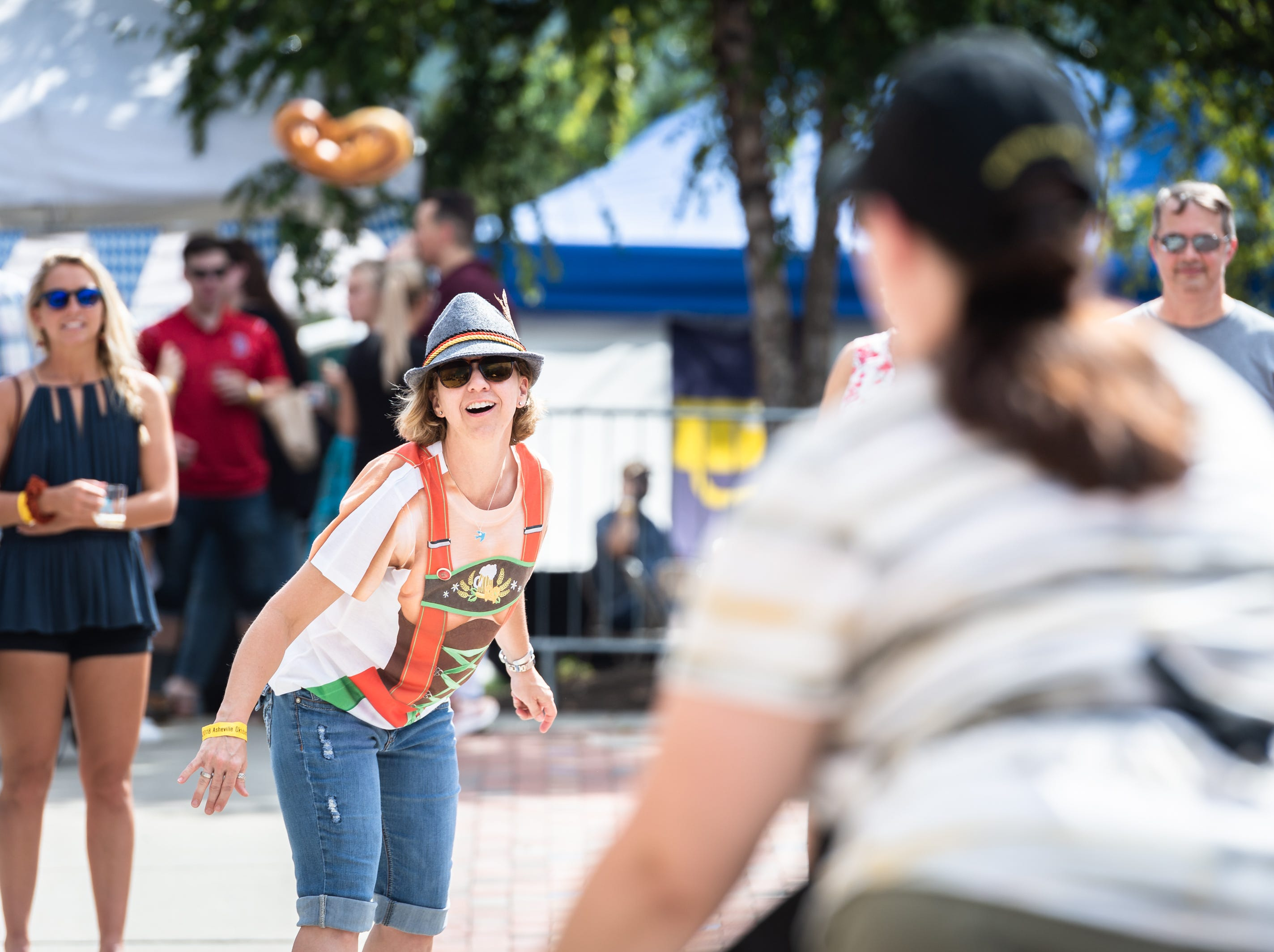 Suzy Milliard tosses a pretzel to her teammate Stacey Heller during the pretzel toss at the 10th annual Asheville Oktoberfest at Pack Square Park Saturday, Oct. 6, 2018.
