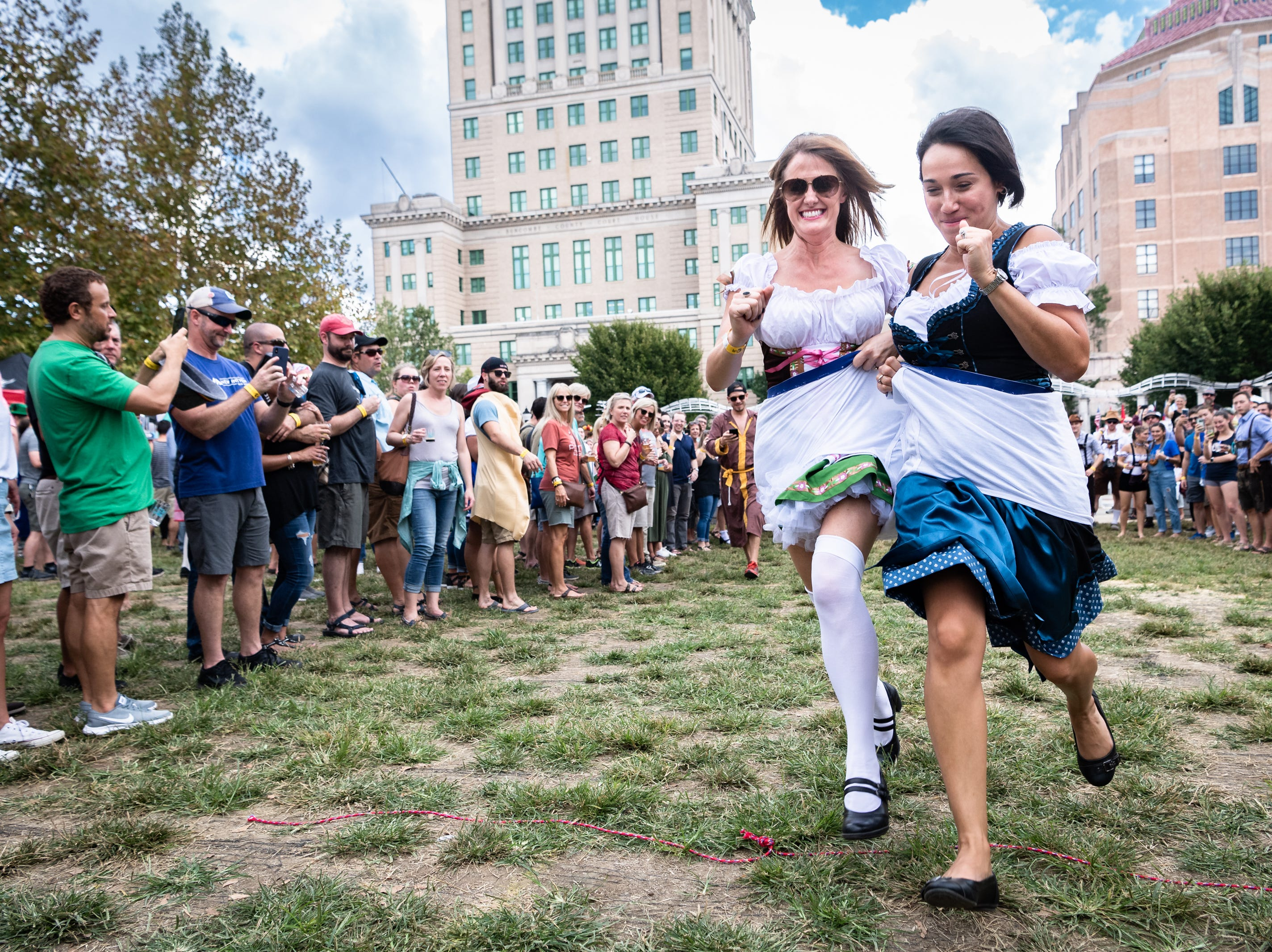 Tricia White and her teammate Marian Keen run across the finish line in a giant pair of underwear during the whitey tighty race at the 10th annual Asheville Oktoberfest at Pack Square Park Saturday, Oct. 6, 2018.