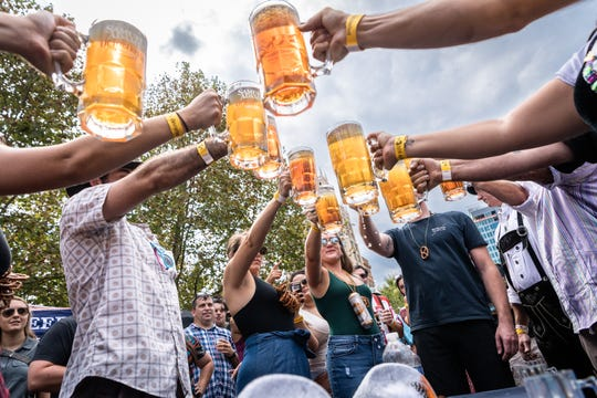 Competitors in the stein hoisting competition at the 10th annual Asheville Oktoberfest, hold out their mugs at Pack Square Park Saturday, Oct. 6, 2018.