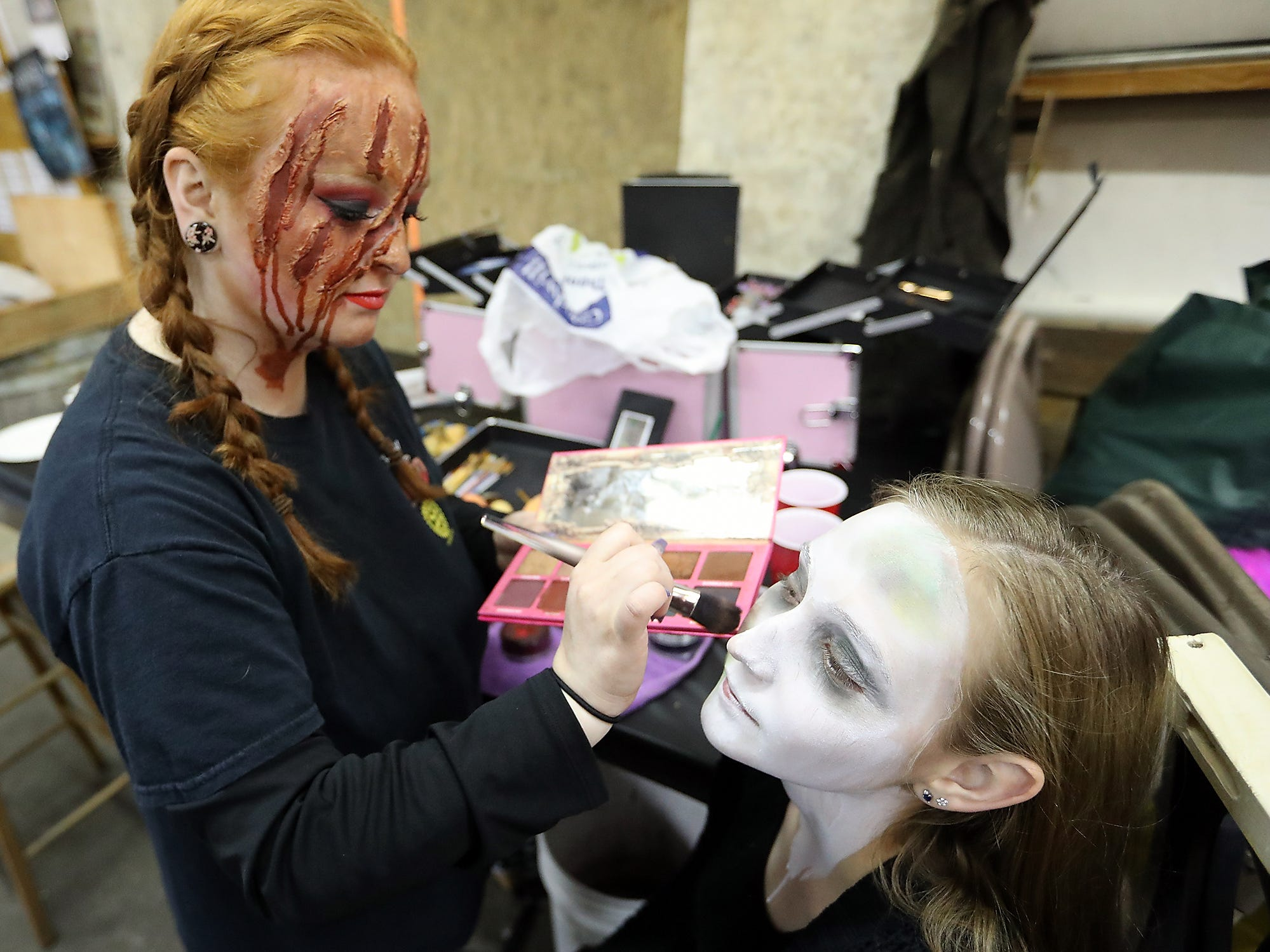 Brianna Miller, left, applies makeup to Marly Regan prior to the start of opening night of the Kitsap Haunted Fairgrounds on Friday, October 5, 2018.
