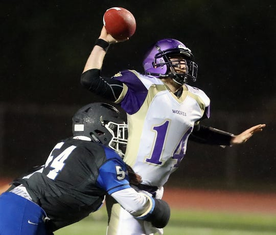 Olympic's Josiah Williams hits Sequim quarterback Riley Cowan during Friday's game at Silverdale Stadium.