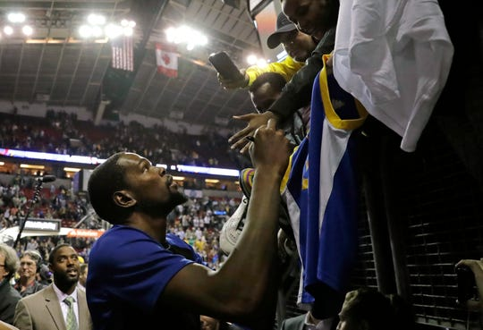 Kevin Durant signs autographs after Friday's NBA preseason game between his Golden State Warriors and the Sacramento Kings at KeyArena in Seattle.