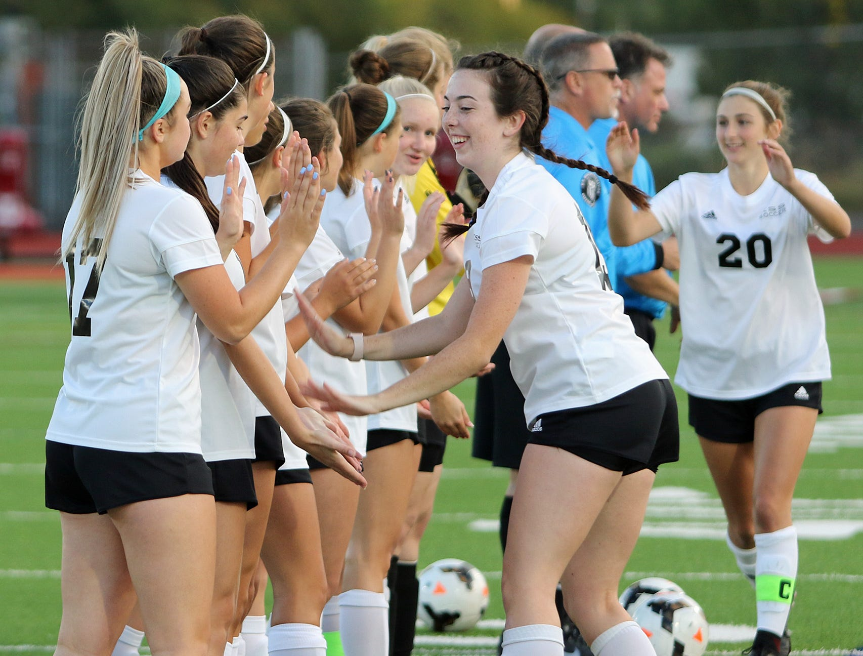 Klahowya soccer players Sheala Haga, front, and Alyssa Peters work their way down the line during team introductions during a recent game against South Kitsap.