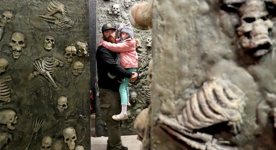 "Joseph Dean carries daughter Scarlett through the catacombs portion of the Kitsap Haunted Fairgrounds on Friday, October 5, 2018. The event hosts a lights on ""no scare"" trip through the venue."