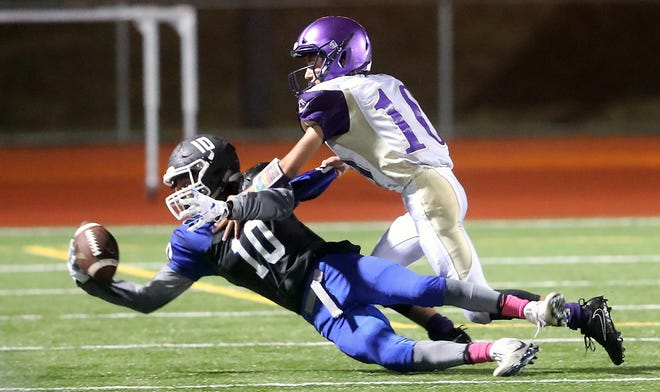 Olympic's Adam Johnson makes a catch while under pressure from Sequim's Garret Hoesel (right) at Silverdale Stadium on Friday, October 5, 2018.