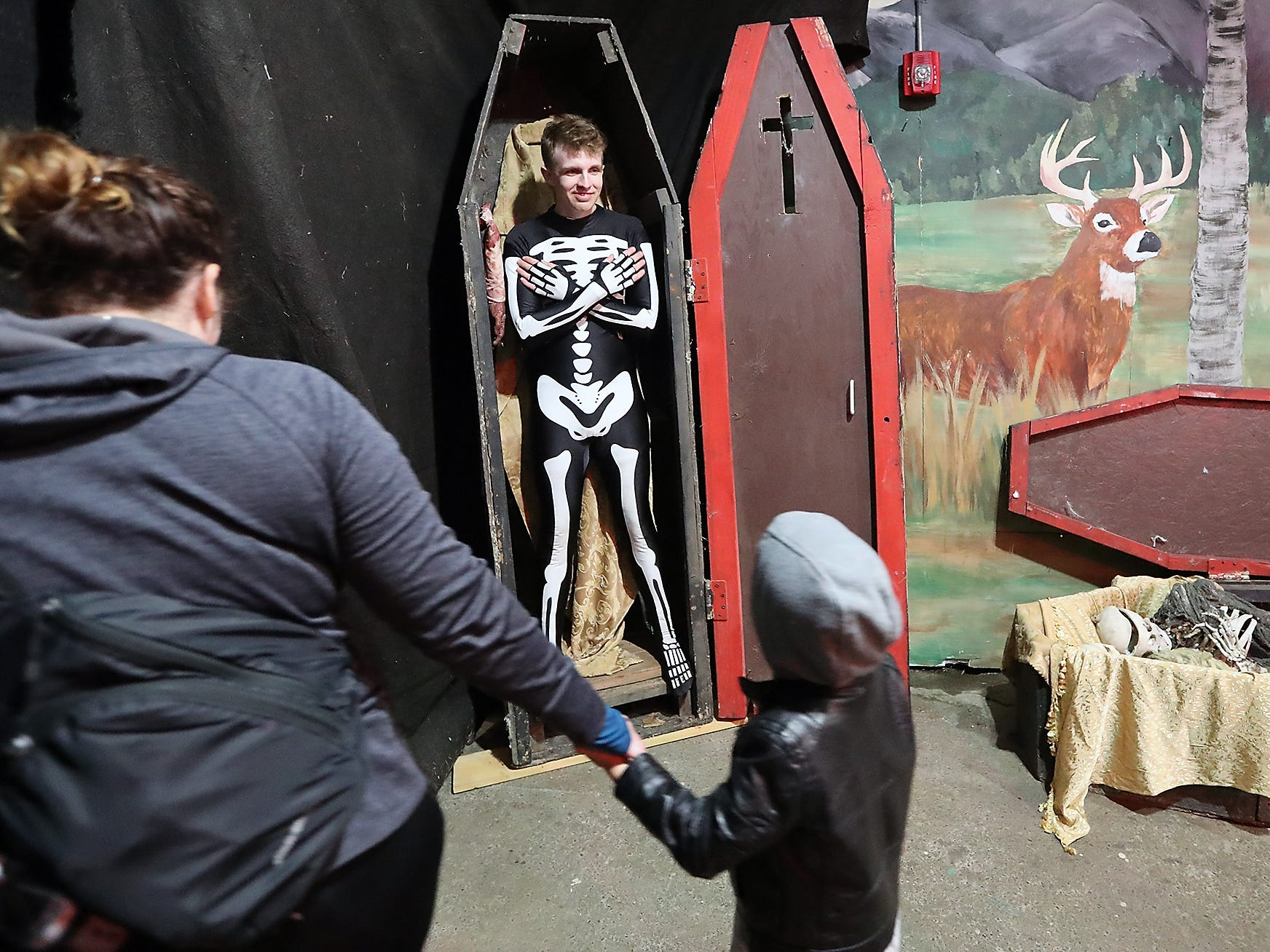 "Jeffrey Dunbar gives a smile to visitors as they pass his coffin during the ""no scare"" part of opening night of the Kitsap Haunted Fairgrounds on Friday, October 5, 2018."