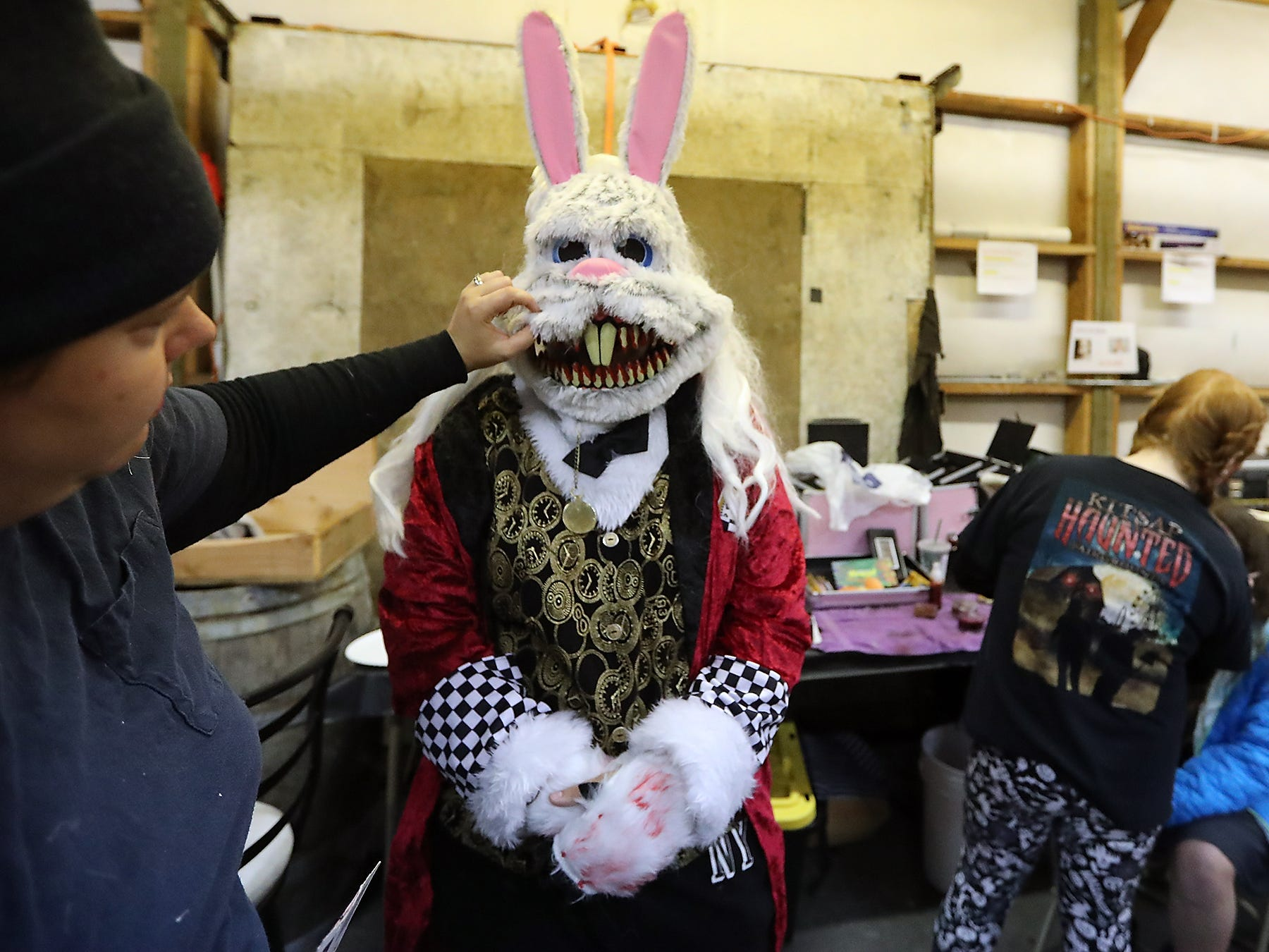 Nicole Wood, left, takes a closer look at the smile of the White Rabbit, played by Selah Shorter, as the cast of the Kitsap Haunted Fairgrounds prepares for opening night on Friday, October 5, 2018. Wood came to the conclusion that the teeth needed a bit more blood makeup added to them.