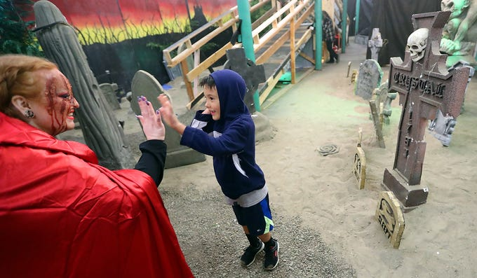 "Dressed as a scary version of Little Red Riding Hood, Brianna Miller gives a high-five to Temujin Weiner, 7, after he bravely completed his trip through the Kitsap Haunted Fairgrounds during their hour-long ""lights on"" portion on Friday, October 5, 2018."