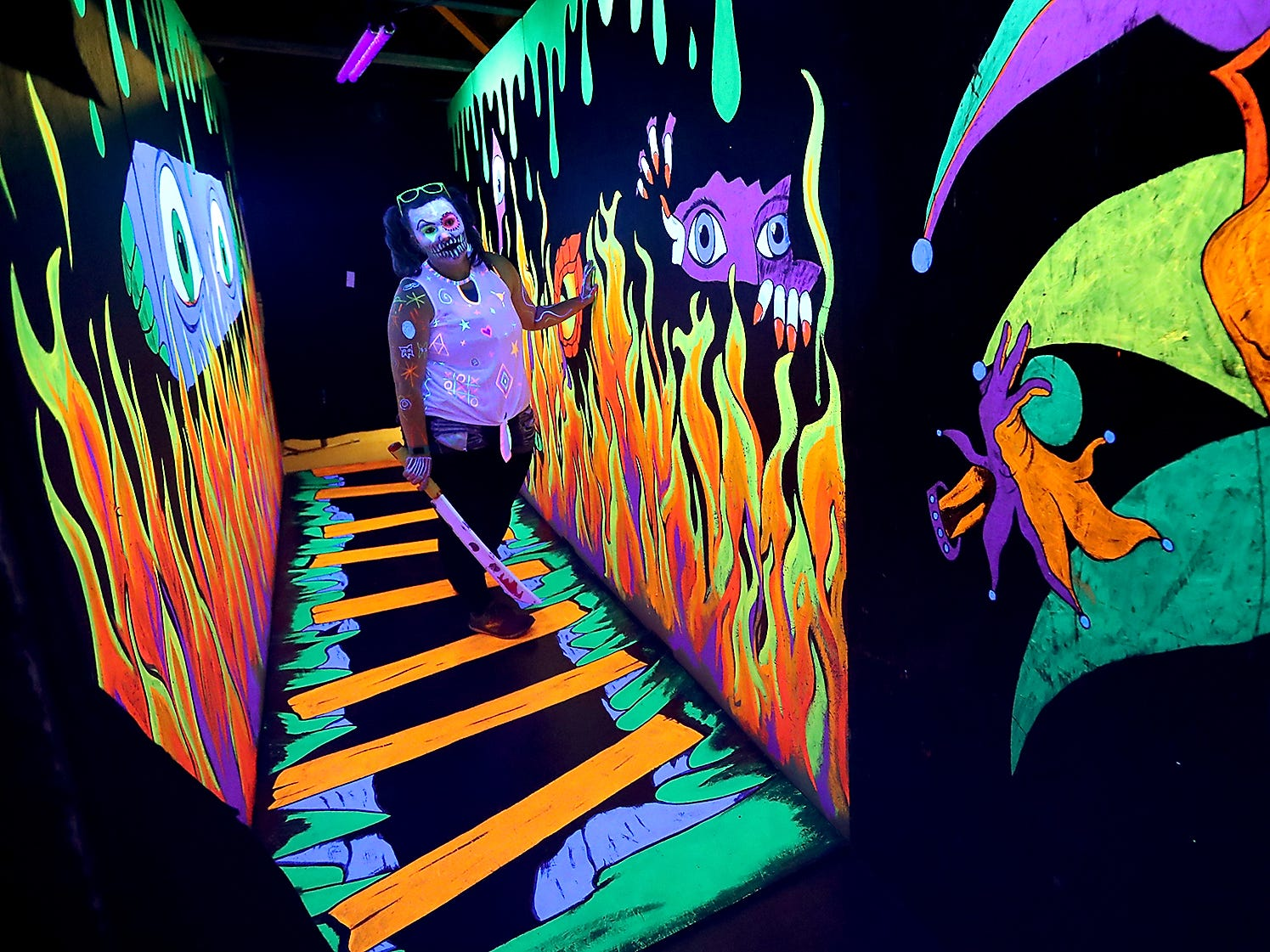 "Megan Jackson plays the part of ""Doodles"" in the black-light hallway during the opening night of the Kitsap Haunted Fairgrounds on Friday, October 5, 2018."