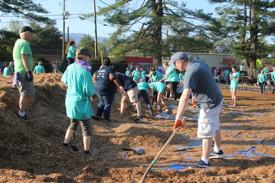 A group of volunteers s[reads mulch around around the new playground at Black Mountain Primary, which was constructed by over 200 community members on Oct. 6.