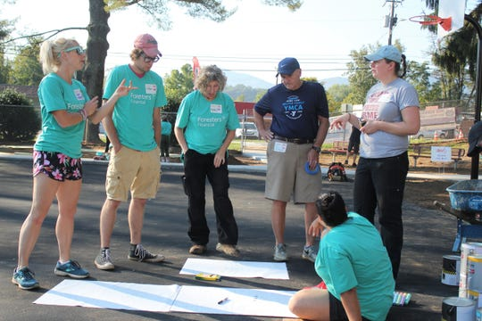 A group of volunteers, including Buncombe County Schools superintendent Tony Baldwin in navy blue, works on designs for the basketball court at Black Mountain Primary as part of the KaBOOM! playground build on Oct. 6.