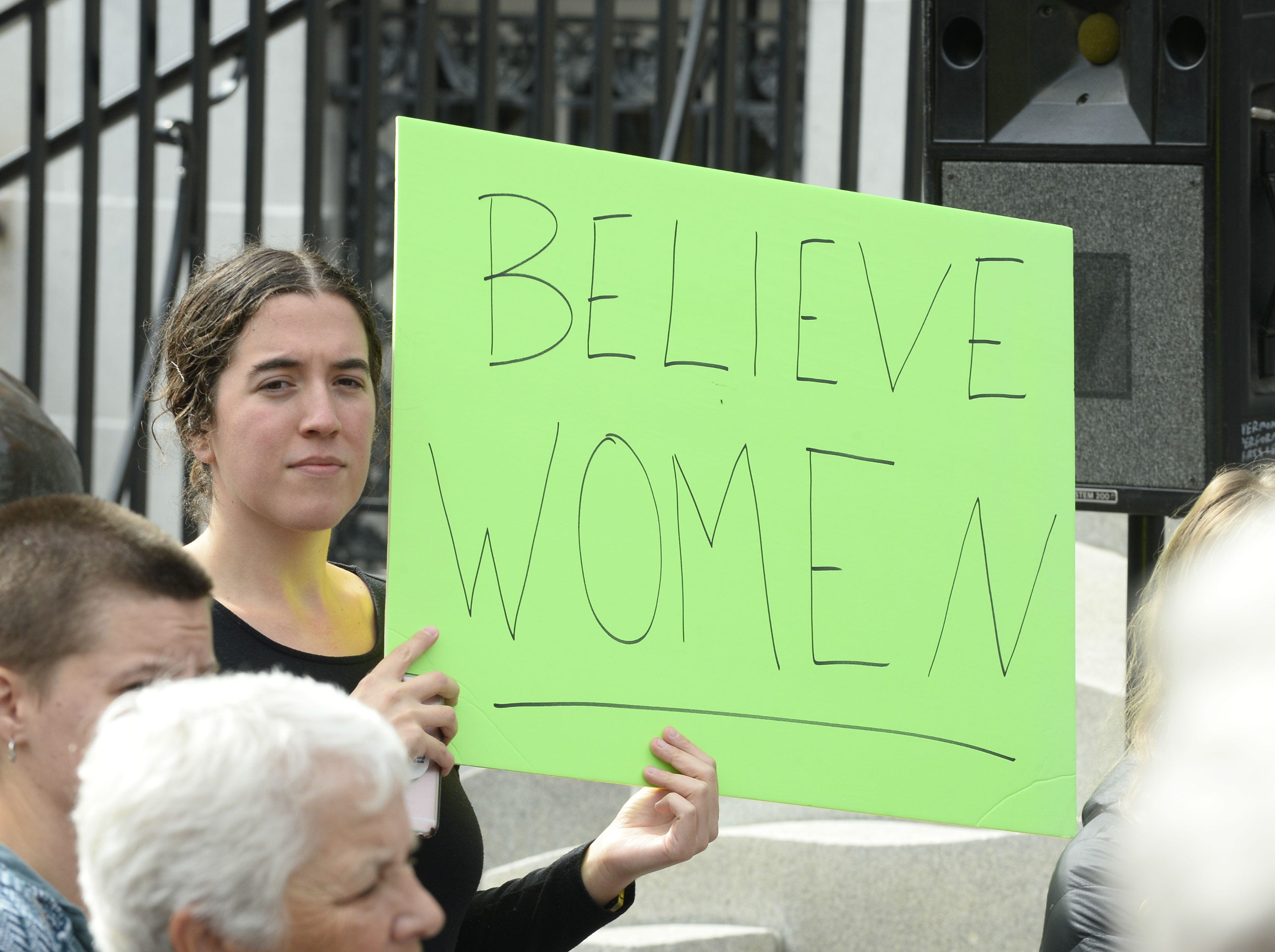A woman holds a sign in front of City Hall as people gather after marching through Burlington Saturday, Oct. 6, 2018, against the confirmation of Supreme Court Justice Brett Kavanaugh. About 100 people turned out for the march down Church Street and around City Hall Park.
