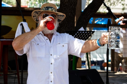 Wayne Croft drinks a beer as he takes part in a beer stein holding preliminary contest at Executive Surf Club during Surftoberfest on Oct. 6, 2018.