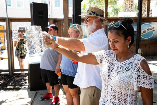 Four people take part in a beer stein holding preliminary contest at Executive Surf Club during Surftoberfest on Oct. 6, 2018.