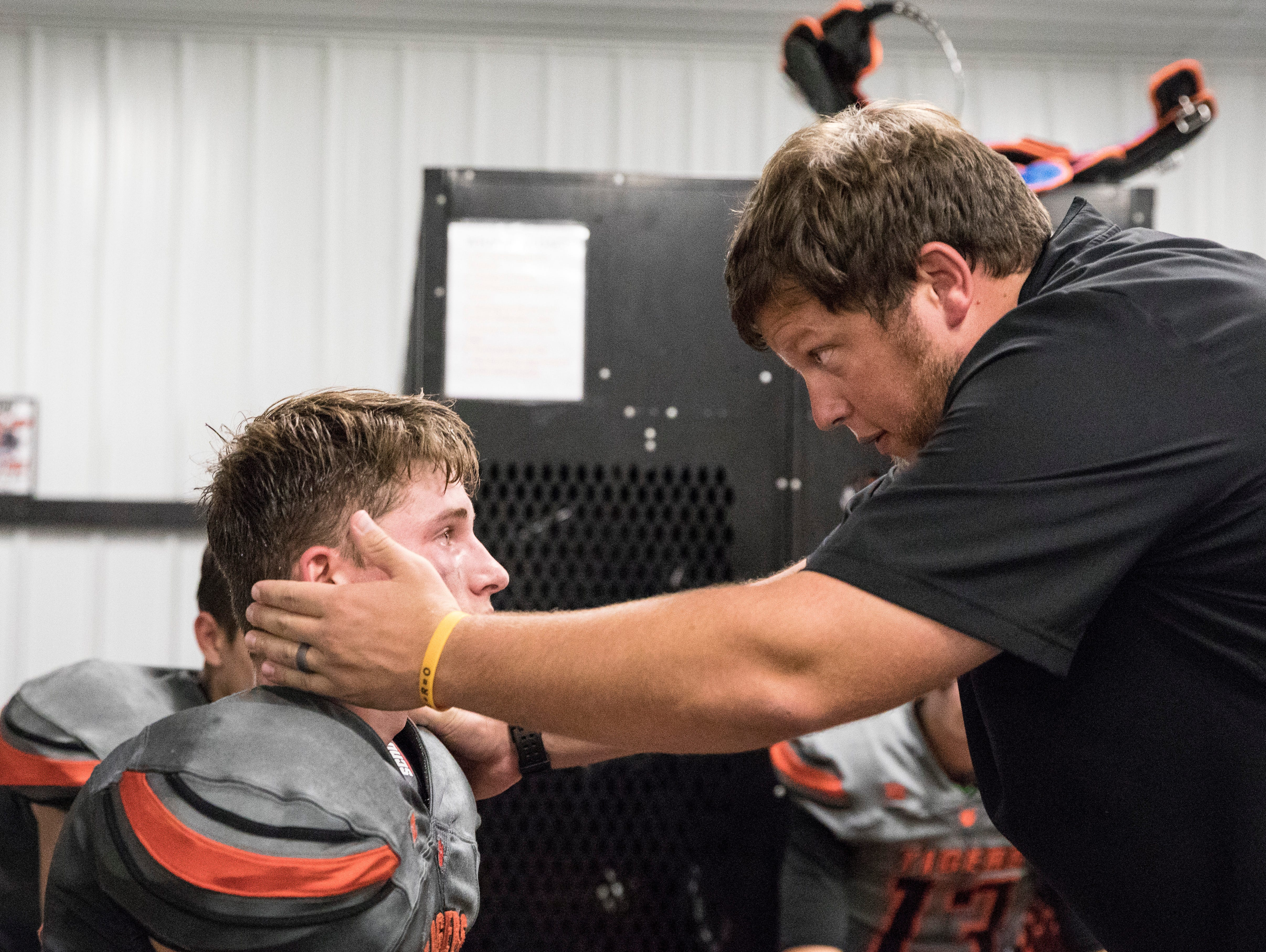 Waverly's Payton Shoemaker has a moment with coach Daniel Sand during the game's first lightning delay of the evening against Wheelersburg with 3:19 left in the first quarter.