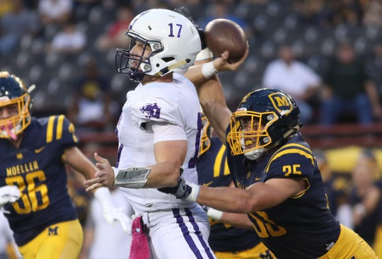 Moeller's Joe Craft (35) hits Elder quarterback Micheal Bittner as he throws the ball during their football game, Friday, Oct. 5, 2018.