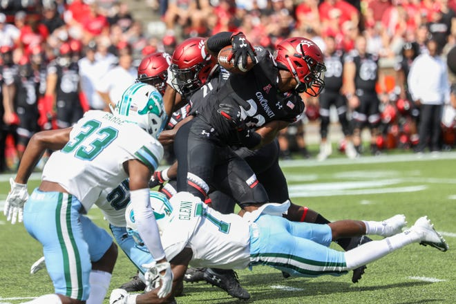 UC's James Wiggins fights through Tulane's defense during the UC vs Tulane game at Nippert Stadium on Saturday Oct. 6, 2018. At halftime, the Bearcats were up 24 - 14.