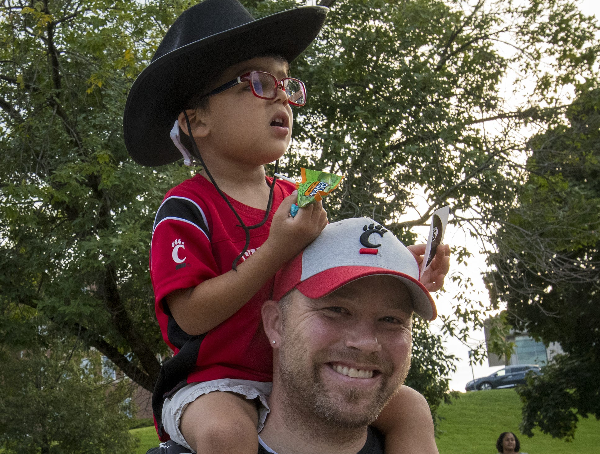Jay Byland and son Elijah, 3, watch the Homecoming parade on Clifton Avenue.