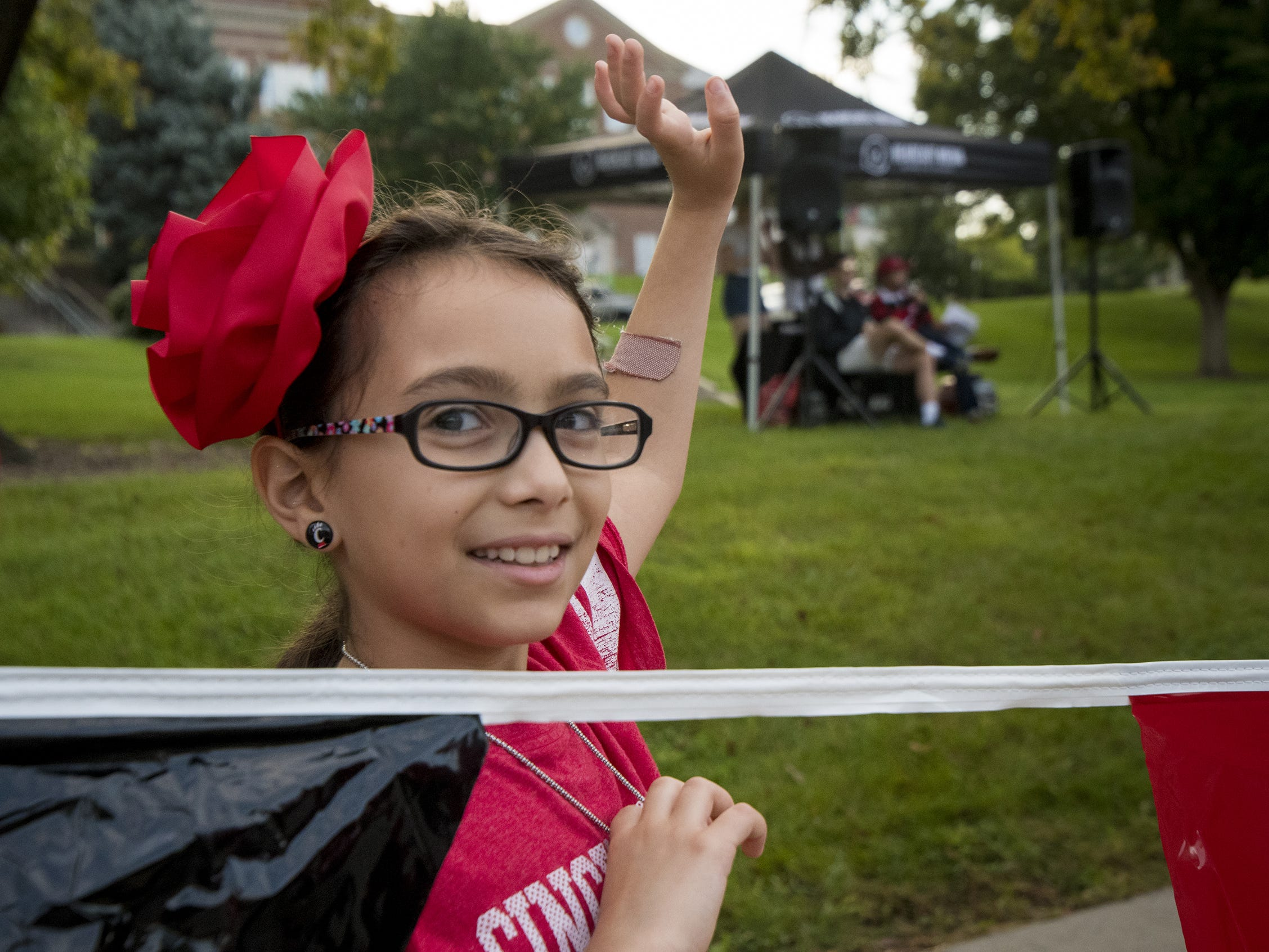 Alejandra Villalva, 9, watches the annual University of Cincinnati Homecoming parade.