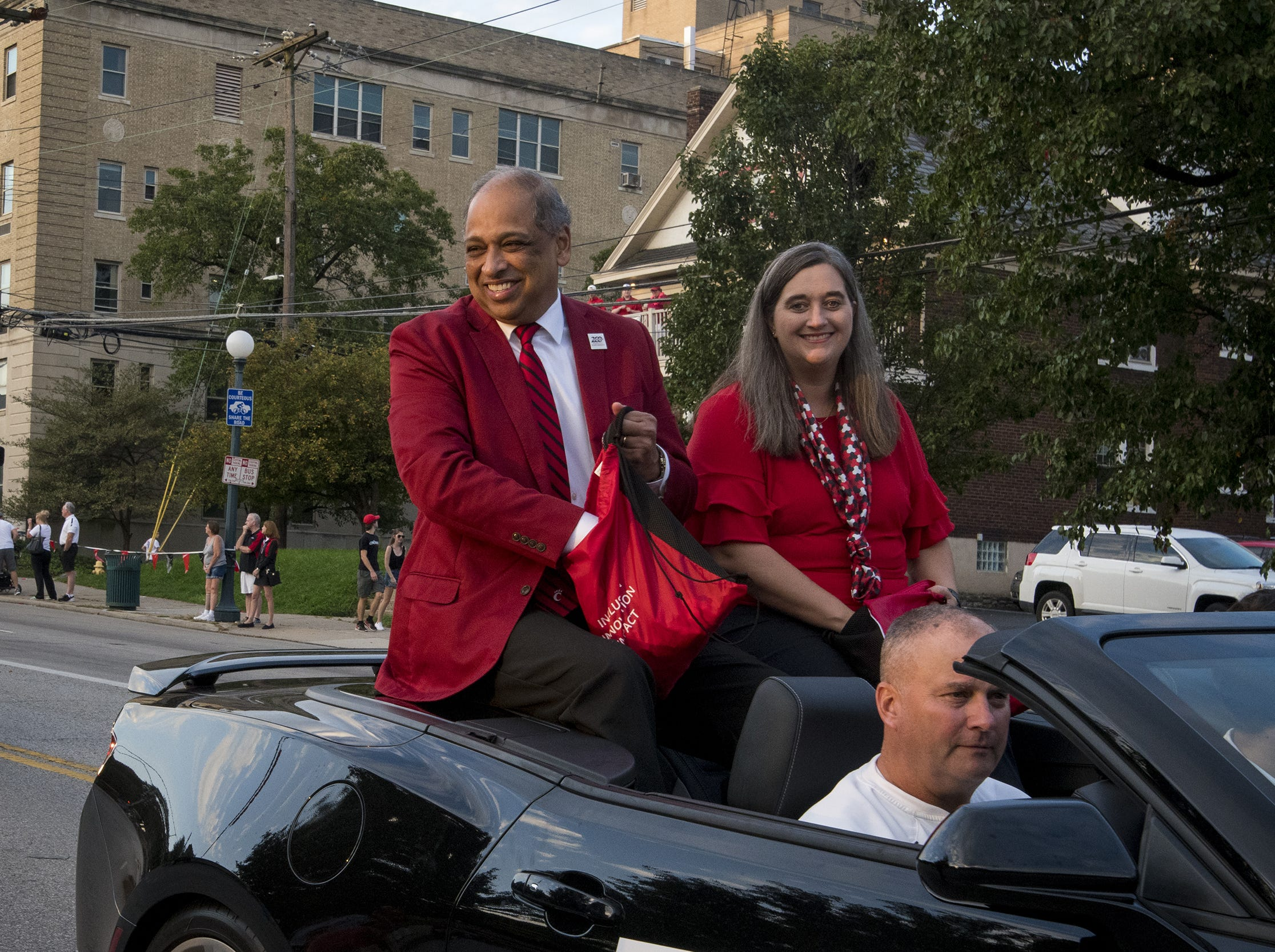 University of Cincinnati President Neville Pinto tosses candy during the annual Homecoming parade.