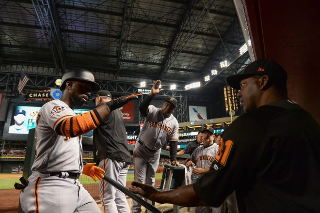 Jun 30, 2018; Phoenix, AZ, USA; San Francisco Giants outfielder Andrew McCutchen (left) is congratulated bench coach Hensley Meulens (31) after hitting a solo home run in the fourth inning against the Arizona Diamondbacks at Chase Field. Mandatory Credit: Jennifer Stewart-USA TODAY Sports