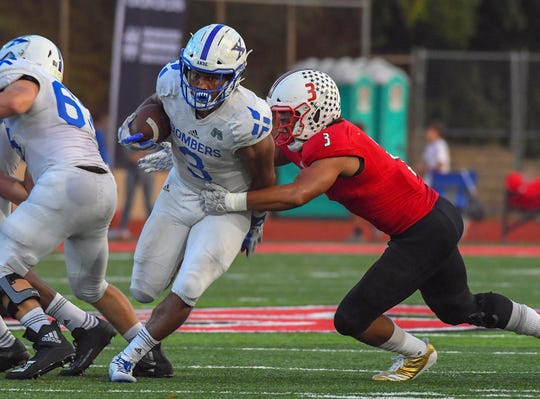 St. X running back Chris Payne runs through the tackle of La Salle defender Deon Campbell for a Bomber touchdown at La Salle High School, Green Township, Friday Oct., 5 2018