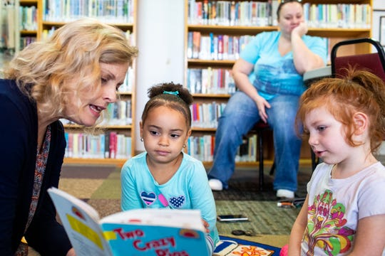 Beth Glover (left) reads to Iyanna Shelby, 4, and Albi Hoover, 4, (right) during class at The Learning Center Monday, Oct. 1, 2018, in Clarksville, Tenn.