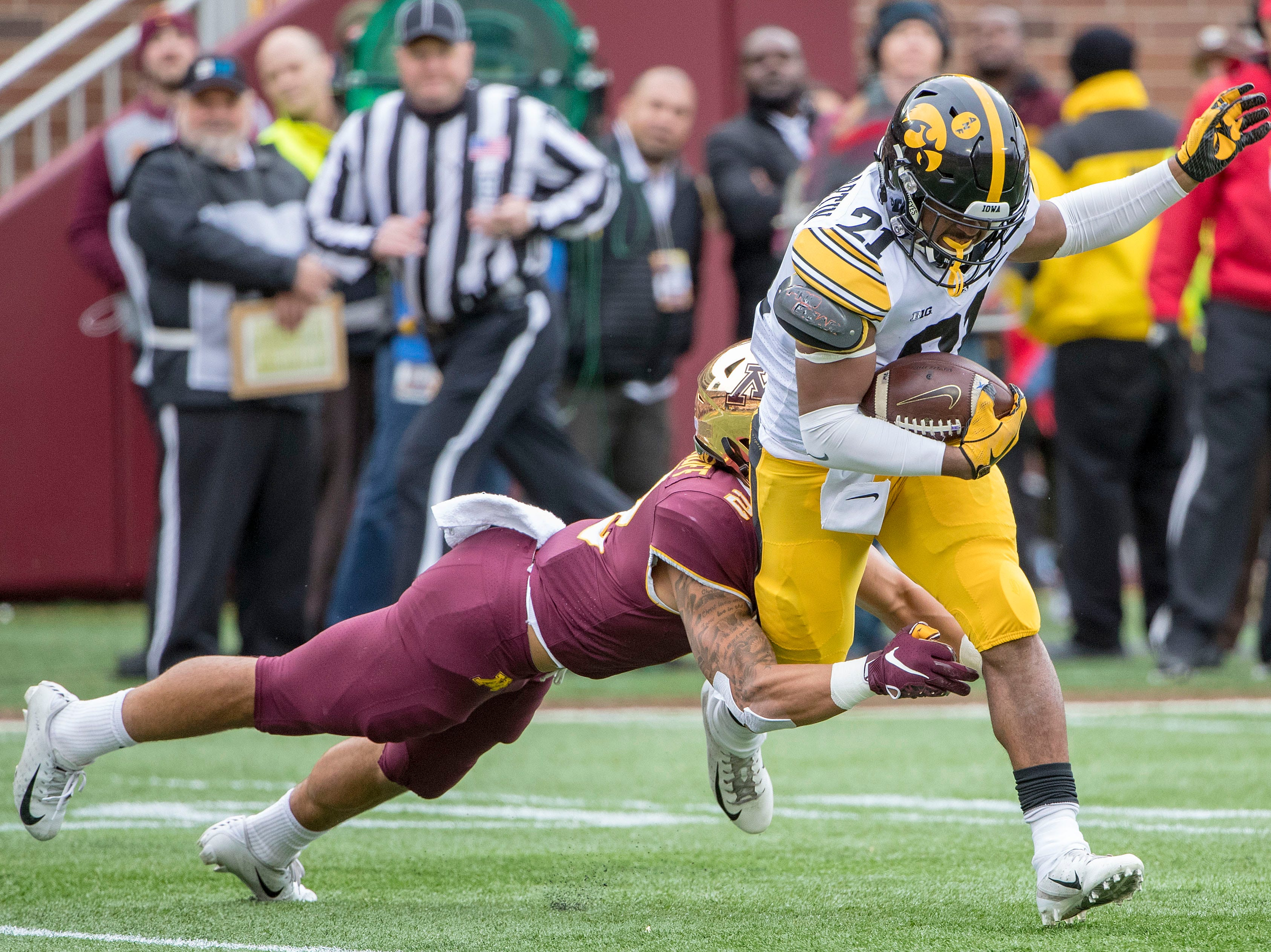 Oct 6, 2018; Minneapolis, MN, USA; Iowa Hawkeyes running back Ivory Kelly-Martin (21) runs the ball as Minnesota Golden Gophers defensive back Jacob Huff (2) makes a tackle in the first quarter at TCF Bank Stadium. Mandatory Credit: Jesse Johnson-USA TODAY Sports