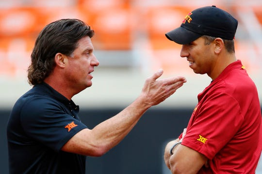 Head coach Mike Gundy of the Oklahoma State Cowboys talks with head coach Matt Campbell of the Iowa State Cyclones before their game on October 6, 2018 at Boone Pickens Stadium in Stillwater, Oklahoma.