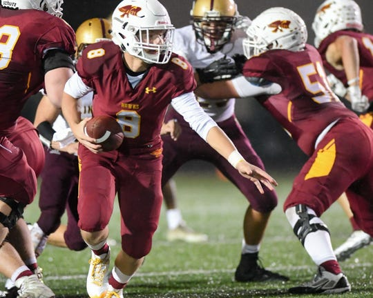 Ankeny Quarterback Jase Bauer (8) fakes a handoff as he rolls back for a pass on Friday, Oct. 5, 2018 during a football game between the Ankeny Hawks and the Lincoln Railsplitters at Northview Middle Stadium.