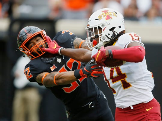 Iowa State wide receiver Tarique Milton (14) fights off a tackle by Oklahoma State cornerback Kris McCune (32) in the second half of an NCAA college football game in Stillwater, Okla., Saturday, Oct. 6, 2018.