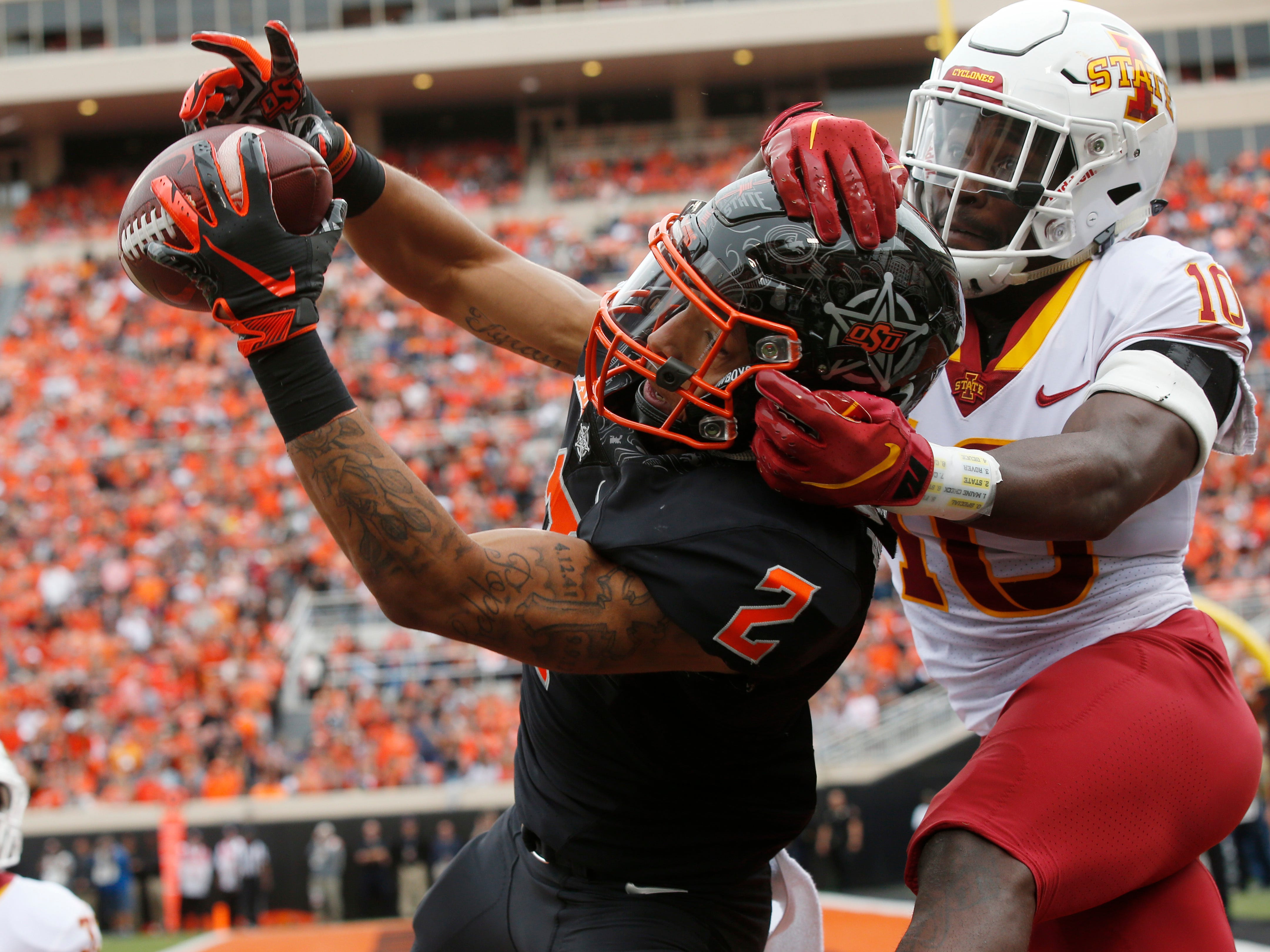 Oklahoma State wide receiver Tylan Wallace (2) reaches for but can't hold onto the pass as he is defended by Iowa State defensive back Brian Peavy (10) in the first half of an NCAA college football game in Stillwater, Okla., Saturday, Oct. 6, 2018.