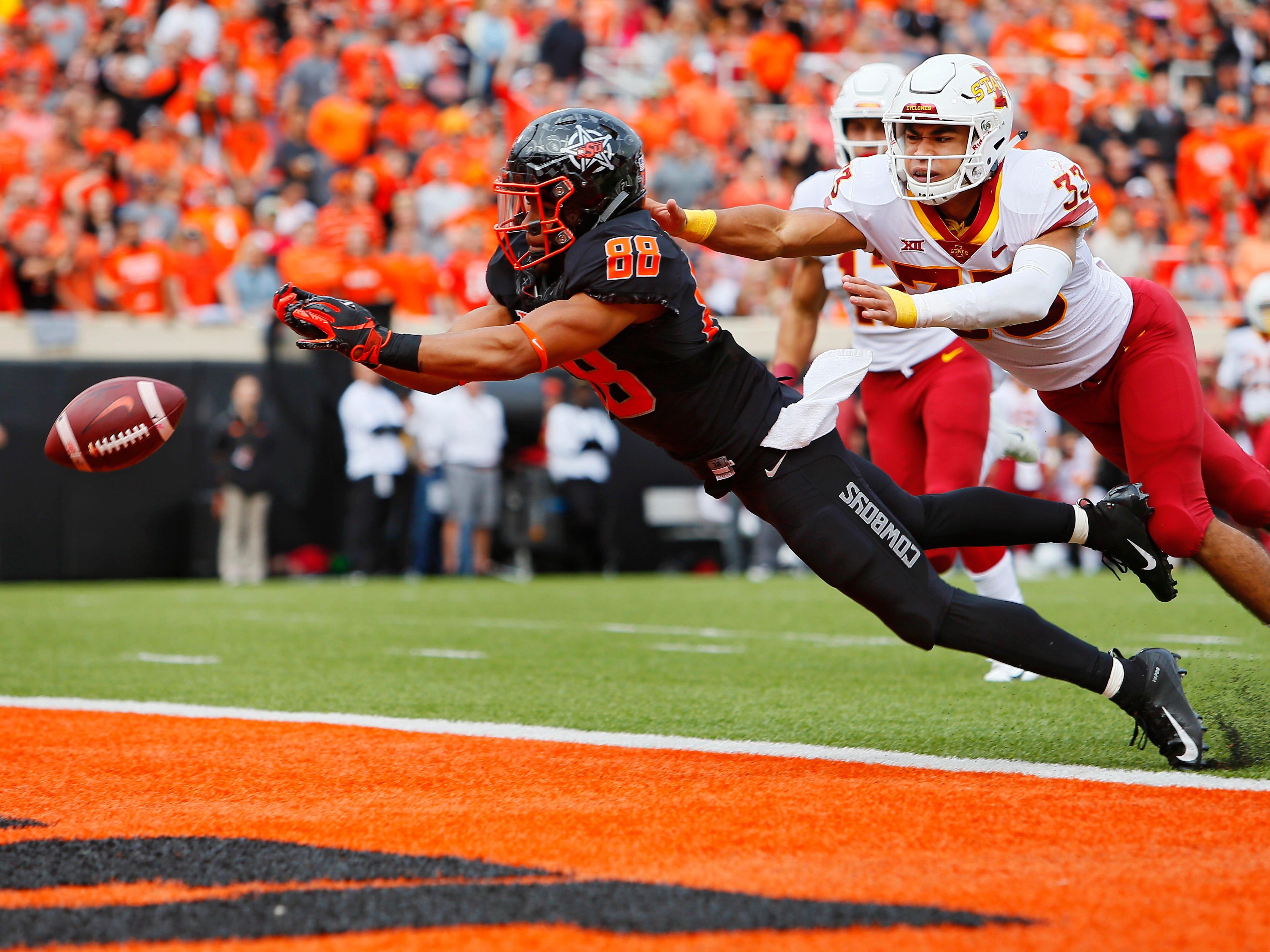 STILLWATER, OK - OCTOBER 6:  Wide receiver Landon Wolf #88 of the Oklahoma State Cowboys stretches only to have the ball go through his fingertips against defensive back Braxton Lewis #33 of the Iowa State Cyclones in the second quarter on October 6, 2018 at Boone Pickens Stadium in Stillwater, Oklahoma.
