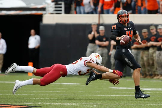 Oklahoma State quarterback Taylor Cornelius (14) is chased by Iowa State linebacker Jake Hummel (35) in the second half of an NCAA college football game in Stillwater, Okla., Saturday, Oct. 6, 2018.