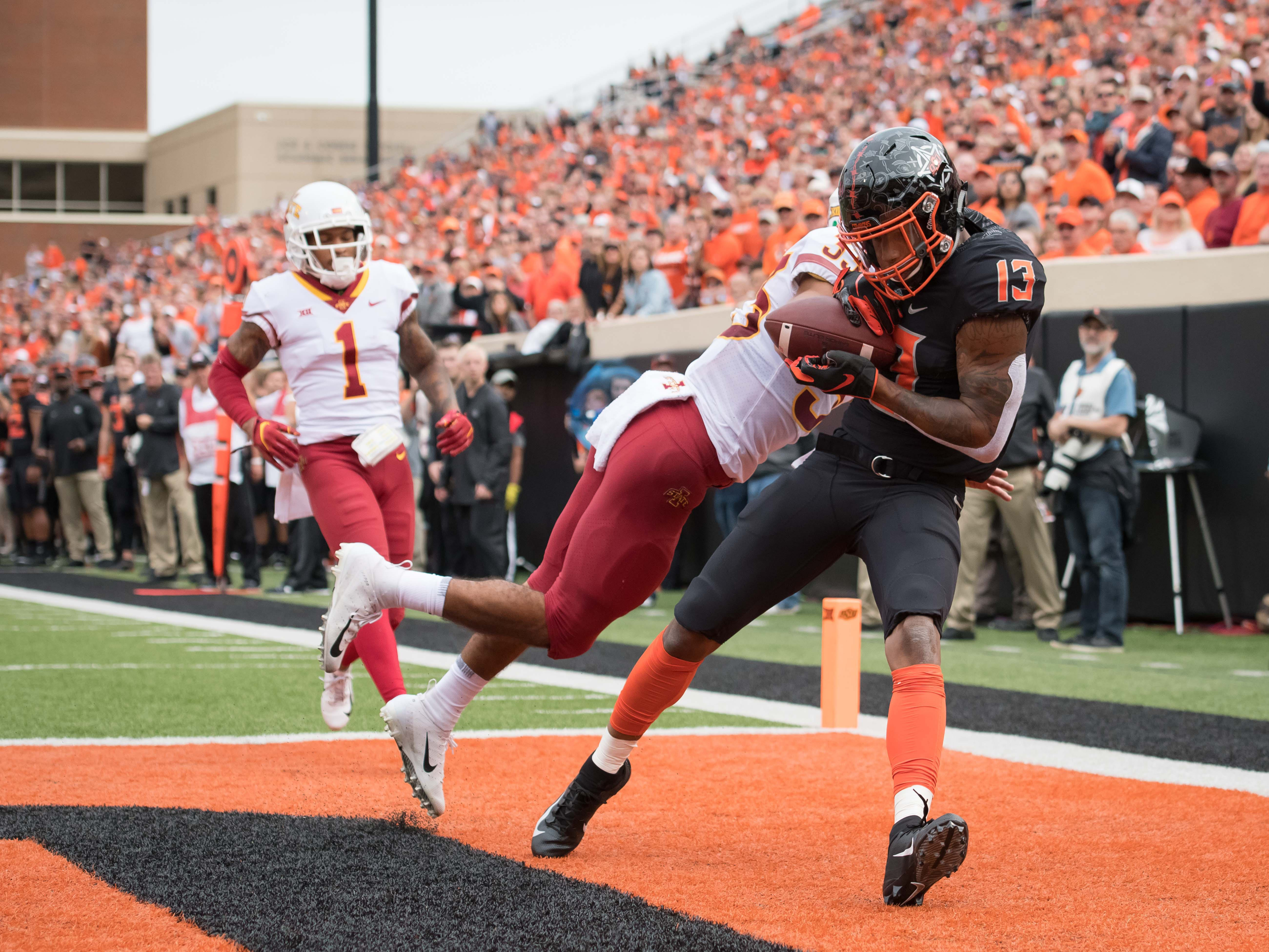 Oct 6, 2018; Stillwater, OK, USA; Oklahoma State Cowboys wide receiver Tyron Johnson (13) makes a catch for a touchdown against Iowa State Cyclones defensive back Braxton Lewis (33) during the first half at Boone Pickens Stadium.