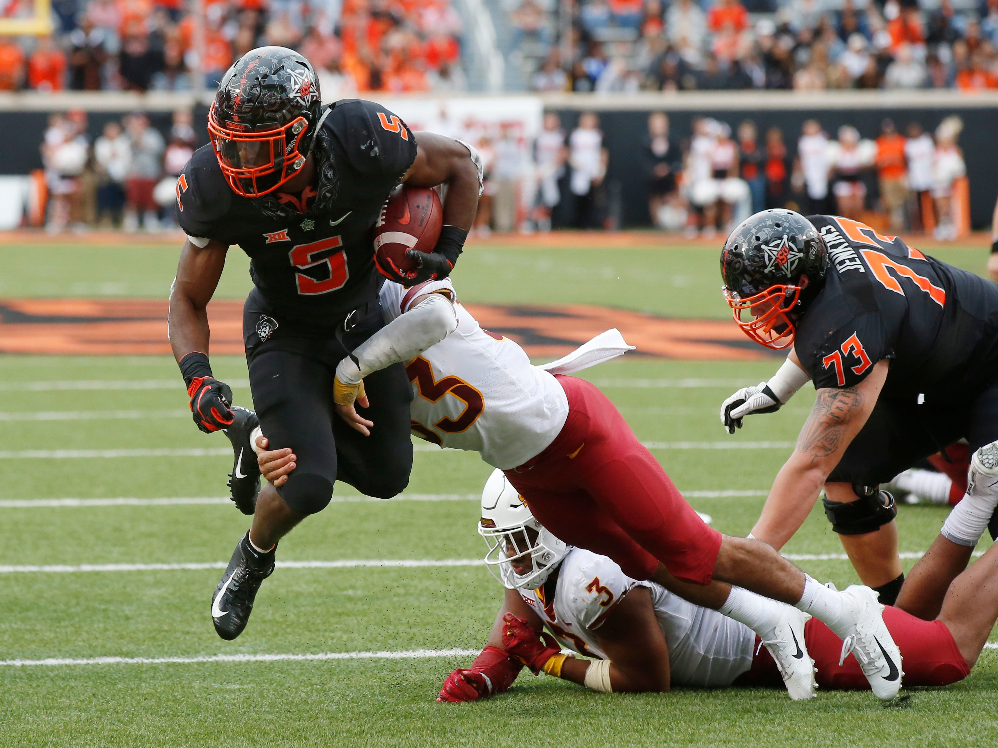 Oklahoma State running back Justice Hill (5) fights a tackle by Iowa State defensive back Braxton Lewis (33) in the second half of an NCAA college football game in Stillwater, Okla., Saturday, Oct. 6, 2018.