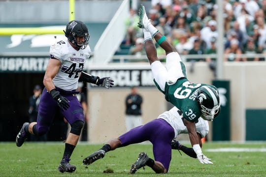 Michigan State running back Alante Thomas tries to keep balance as he's defended by Northwestern linebacker Paddy Fisher (42) and safety JR Pace (13) during the first half at Spartan Stadium in East Lansing, Saturday, Oct. 6, 2018.