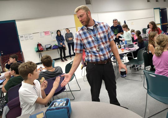 Gabe, left high fives assistant principal Jason Hill during lunch in the school cafeteria at Birmingham Covington School in Bloomfield Township on Thursday, October 4, 2018