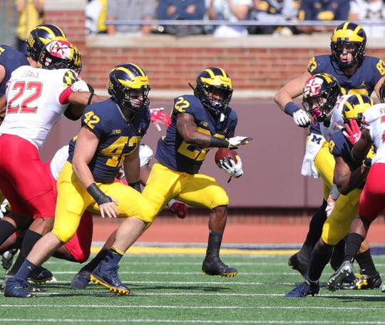 Karan Higdon runs behind a block from Ben Mason (42) in the first half.