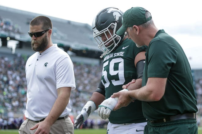 Michigan State guard David Beedle is taken off the field due to a left arm injury during the first quarter against Northwestern at Spartan Stadium, Saturday, Oct. 6, 2018.