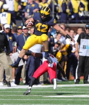 Michigan's Ben Mason jumps over Maryland's Marcus Lewis during the first quarter Saturday, Oct. 6, 2018 at Michigan Stadium in Ann Arbor.
