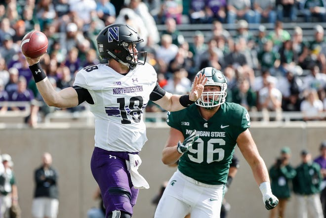 Northwestern quarterback Clayton Thorson makes a pass as Michigan State defensive end Jacub Panasiuk rushes during the first half at Spartan Stadium in East Lansing, Saturday, Oct. 6, 2018.