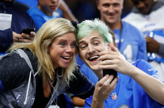 """Tyler """"Ninja"""" Blevins takes photographs with fans before an NFL football game between the Detroit Lions and New York Jets in Detroit, Monday, Sept. 10, 2018. Blevins is a professional Battle Royale Player and streamer on Twitch."""