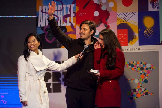 "Mariano Cortez waves as he and his wife Chelsea Nix are awarded the $200,000 public vote grand prize for their work ""THE STRING PROJECT,"" during the 10th international ArtPrize awards ceremony in Grand Rapids."
