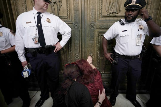 Two activists become emotional after they occupied the foyer of the U.S. Supreme Court to protest against the confirmation of Judge Brett Kavanaugh to the Supreme Court October 6, 2018 in Washington, D.C.