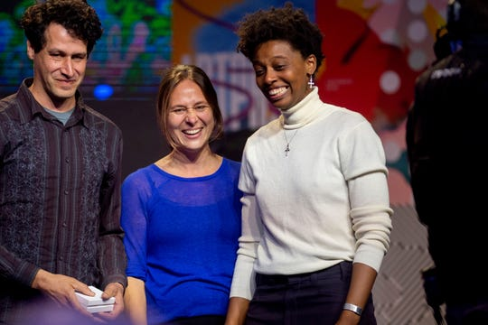 "Le'Andra LeSeur, far right, smiles as she is awarded the $200,000 Juried Grand Prize for her work ""brown, carmine, and blue"" during the ArtPrize 10 awards ceremony in Grand Rapids."