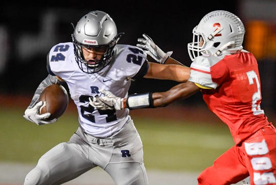 Reitz's Andrew Word (24) tries to escape the grasp of Bosse's Tashmond Starks (2) as the Reitz Panthers play the Bosse Bulldogs at Enlow Field Friday, October 5, 2018.