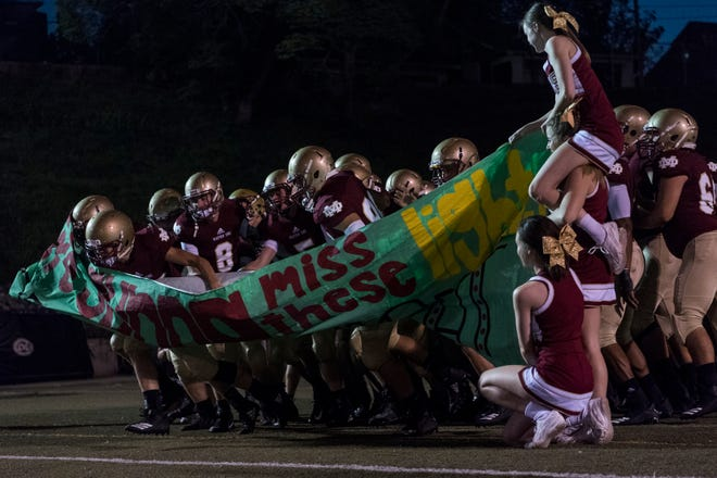 The Mater Dei Wildcats tear open a banner in honor of senior night as they rush the field to take on the Central Bears at the Reitz Bowl in Evansville, Ind., Friday, Oct. 5, 2018. The Bears defeated the Wildcats, 42-7.