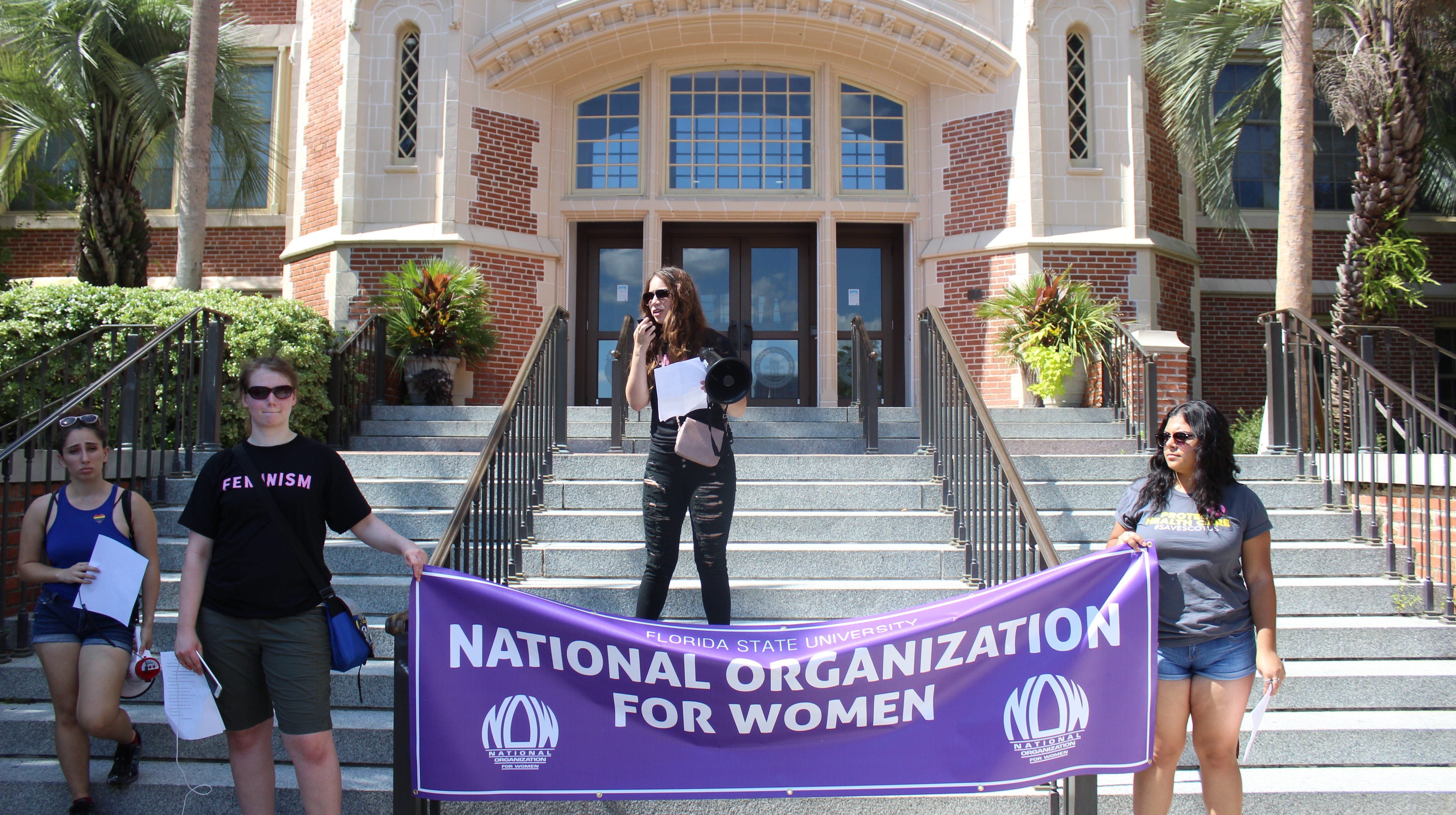 Member of the National Organization for Women hold a banner in front of the Westcott before leading the march to the Capitol.