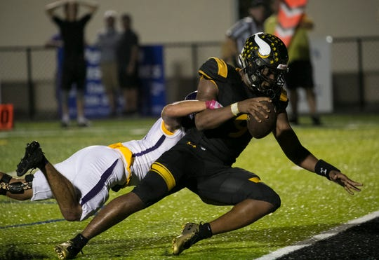 Joslyn Mira of Bishop Verot scores a touchdown as he is tackled by Lucas Marques of Cypress Lake on Friday night, October 5, 2018, at Bishop Verot High School.